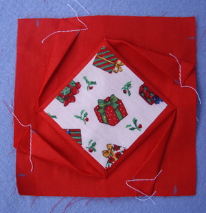 8) Pin 2 1/4 inch square onto the center square of the folded block and trim the 2 1/4 inch square so there is about 1/8 inch of the folded block showing on all sides.