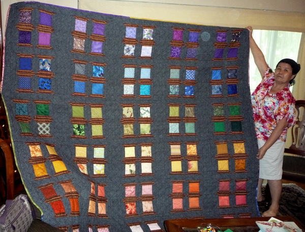 Tiew's sister Dang holds up the beautiful quilt